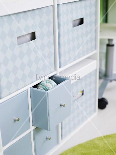 Viel Stauraum in Regal mit grau bedruckten Kisten und kleinen Schubladen