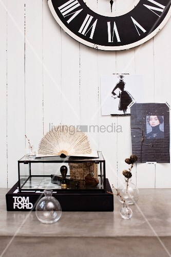 Vintage decor on concrete desk; fashion pictures and wall clock on white wood panelling