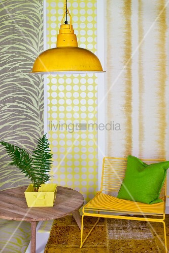 House plant on wooden table, yellow chair and yellow pendant lamp in front of strips of different wallpapers