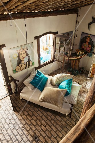 View from gallery down onto pale brick floor and bed with turquoise silk scatter cushions; paintings of Brazilian Candomble sea goddess on walls