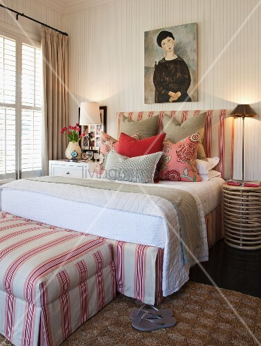 Double bed and matching ottoman in pink and white stripes with various scatter cushions on bed and portrait of woman on wall above