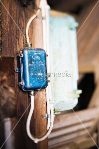 Close-up of simple electrical wiring on wooden wall
