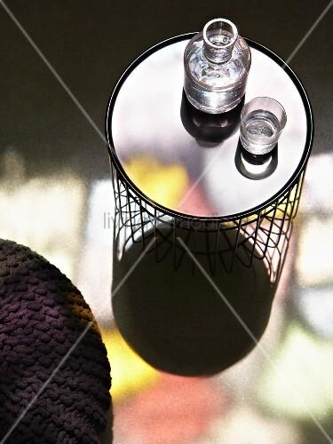 wasserkaraffe und glas auf beistelltisch mit drahtgestell bild kaufen living4media. Black Bedroom Furniture Sets. Home Design Ideas