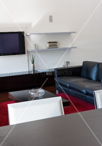 Modern living room with black sideboard and black leather couch; red woollen rug on floor