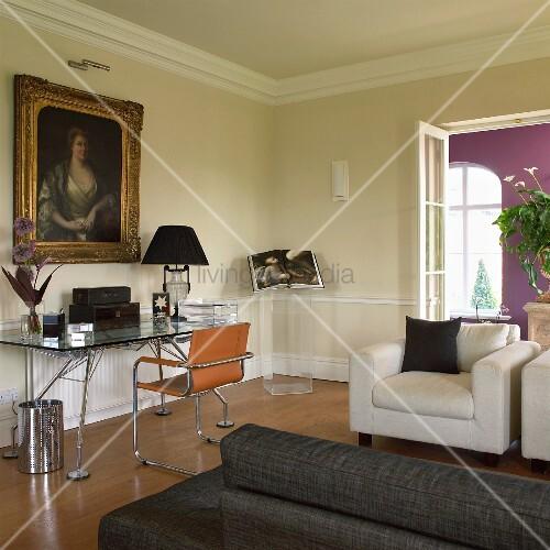 Modern, designer furniture in living room with gilt-framed portrait of woman