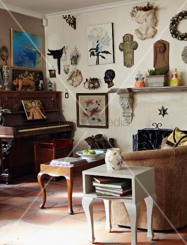 Decorative collector's items and pictures on living room wall above antique piano and vintage-style couch, coffee table and side table
