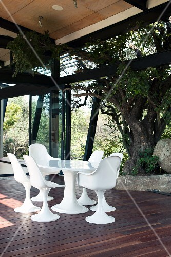 Seating area with white, Bauhaus-style shell chairs on wooden terrace with view into garden