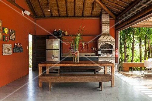 Kitchen with dining area and barbecue on terrace of beach house