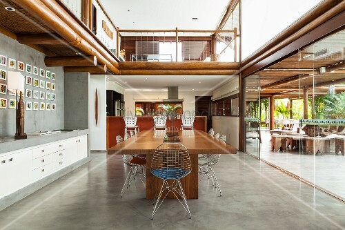 Open-plan living area with dining table and chairs next to glass wall leading to terrace