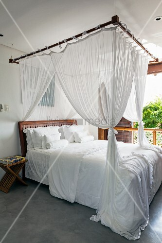 Four-poster bed with white bed linen in white bedroom