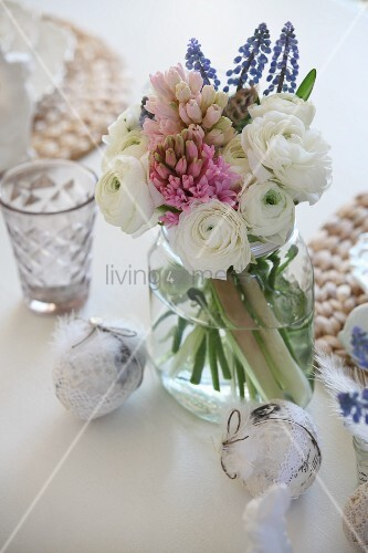 Spring bouquet with white ranunculus and hyacinths in screw-top jar and ornamental eggs decorated with lace ribbons and feathers on table set for Easter