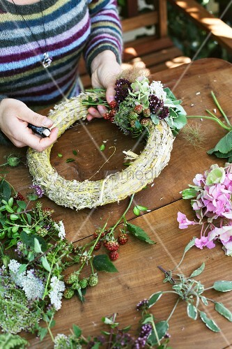 Decorating straw wreath with flowers and blackberries