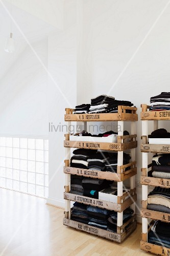 Stacked fruit crates used as creative shelves for clothing in loft-style bedroom