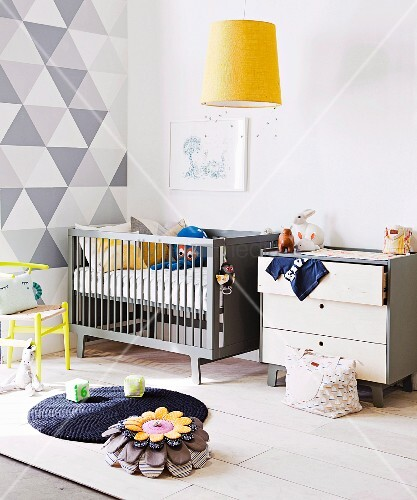 Pale grey chest of drawers and cot against wall with white and grey geometric pattern; yellow pendant lamp above rug and cushion on floor