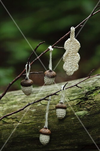 Crocheted acorns and leaf hanging on twig
