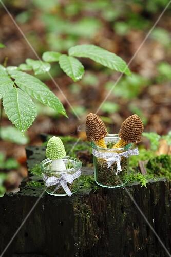 Gehäkelte Pilze in Glas auf bemoostem Baumstamm