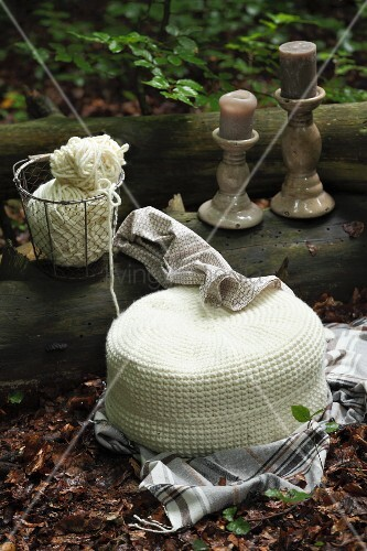 White, crocheted pouffe and candlesticks on tree trunk in woodland