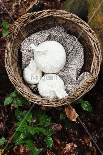 Wicker basket with white, crocheted apples on woodland floor