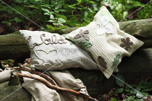 Various embroidered, crocheted and appliqué cushions on tree trunk in woodland