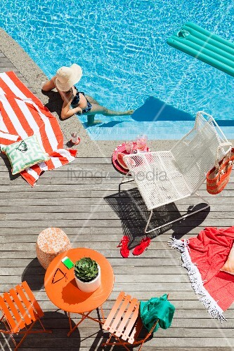 Relaxing by the pool - orange terrace furniture and white wire mesh chair on sunny wooden terrace