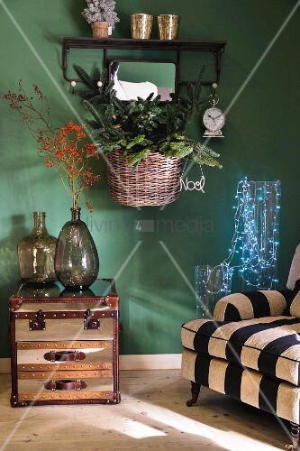 Striped armchair, fairy lights in glass vessels, demijohns on side table and basket of Christmas decorations on green wall