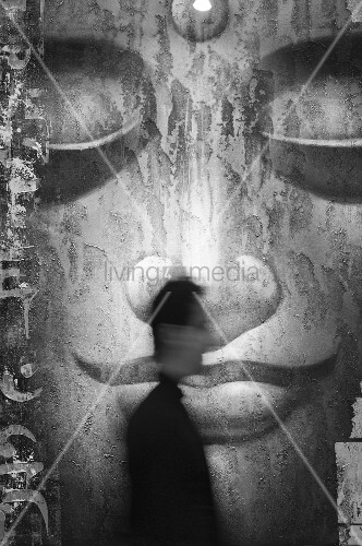 Large size, black and white projection of the face of a Buddha; in front a blurry image of a man in profile