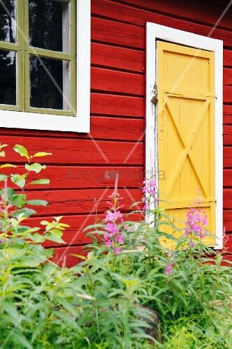 Red Scandinavian wooden house with yellow door
