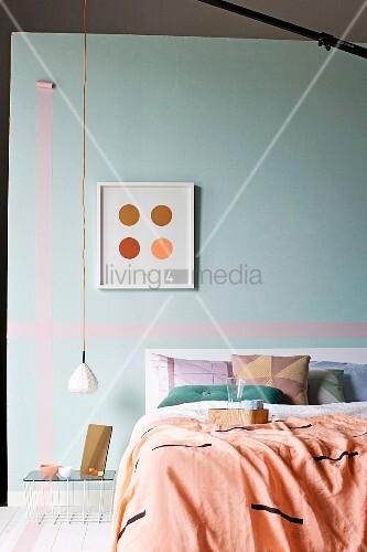 Bett mit Plaid und Kissen vor Wand in pastellfarbenem Türkis mit Masking Tape, minimalistische Pendelleuchte