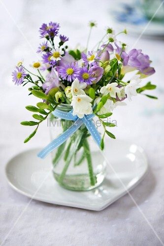 Posy in jar on heart-shaped dish on wedding reception table