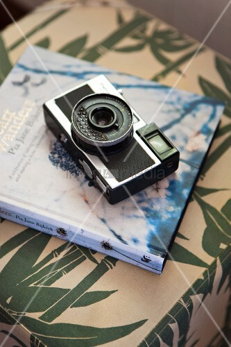 Old camera on book on pouffe
