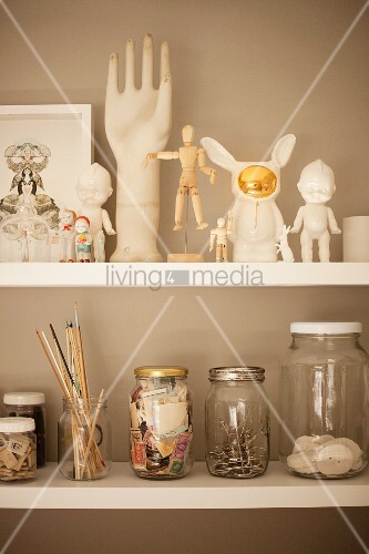 Ornaments and storage jars on white shelves