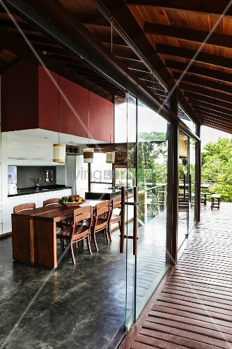 Übergang mit rahmenlosen Glasschiebeelementen zwischen zeitgenössischer, offener Küche mit ...