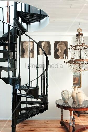 Black, metal, vintage spiral staircase next to various ceramic vases on table below chandelier