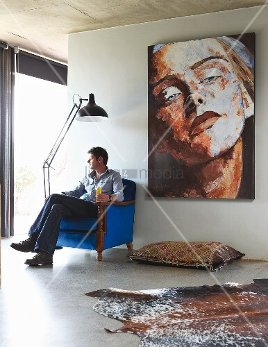 Man sitting in antique armchair upholstered in royal blue; kilim floor cushion below large portrait of woman