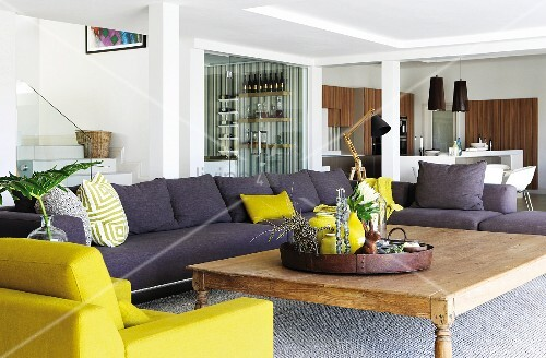Purple-grey sofa and yellow armchair around rustic wooden coffee table in spacious living room with dining area behind pillars