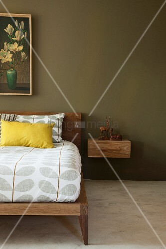 Bed with wooden frame and retro-patterned bed linen and floating bedside cabinet below picture on green-painted wall