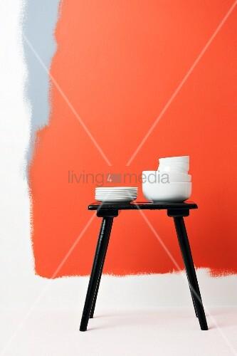 Weisse porzellanstapel auf schwarzem hocker vor rot und - Flecken weisse wand entfernen ...