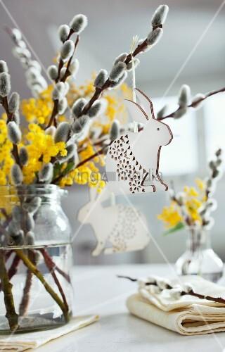 Weidenkätzchen mit Mimosen und Osterhasen-Anhängern als Tischdeko