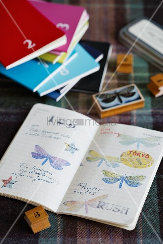Nostalgic wooden stamps with butterfly and number motifs, various books and prints in open book