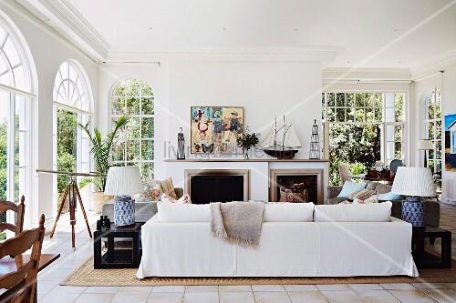 Weisses Sofa vor offenem Kamin in elegantem, traditionellem Wohnzimmer mit Rundbogen ...