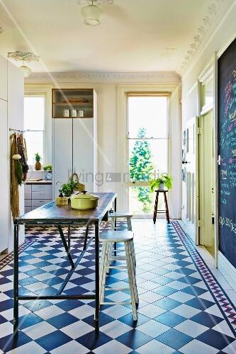 Küche mit schlichtem Metall-Küchentisch und Barhockern auf diagonal ...
