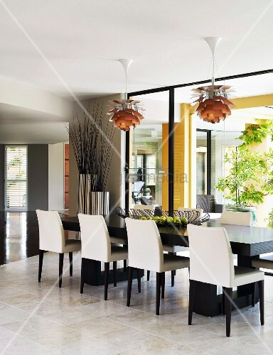 Elegant black and white dining chairs around long table below Bauhaus pendant lamps next to glass wall