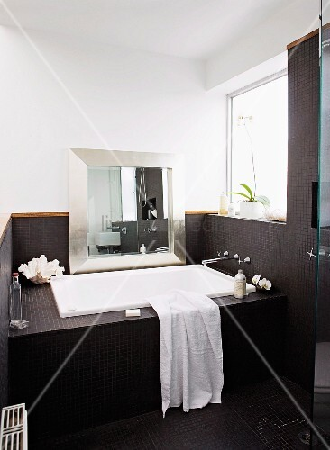 Badewanne In Nische Mit Fenster Eingebaut, Spiegel Mit Silberrahmen An Wand  Lehnend, Frontansicht Der Badewanne Und Wände Mit Schwarzen Mosaikfliesen