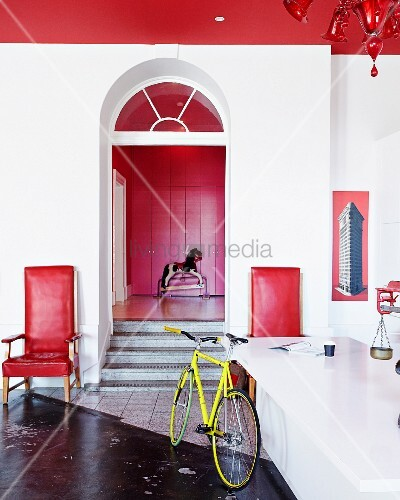 Bicycle leaning against counter opposite doorway with steps flanked by red armchairs; rocking horse in front of red fitted cupboards in background