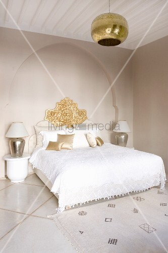 Elegant, white bedroom with double bed against wall niche in shape of Oriental arch