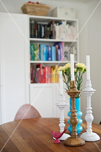 Turned candlesticks and blue vase of carnations on wooden table; bookcase in blurred background