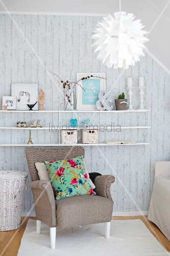Seating area with shelves of vintage ornaments on exposed concrete wall, armchair with floral scatter cushion and Scandinavian designer lamp