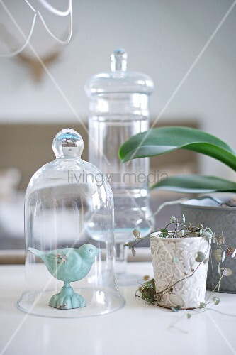 Bird figurine under glass cover next to ornate plant pot and orchid leaves