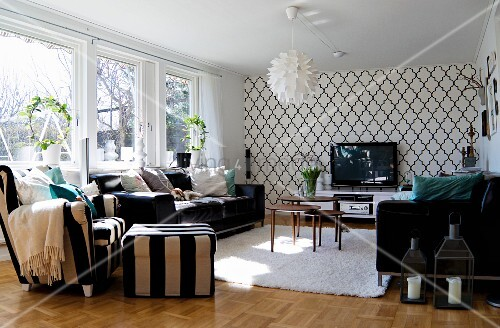 Scandinavian, designer pendant lamps and wallpaper with Oriental ogee pattern in living room furnished in black and white