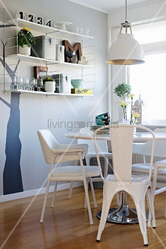 Dining area with white retro furniture, glasses and vintage ornaments on shelves against tree trunk silhouette mural